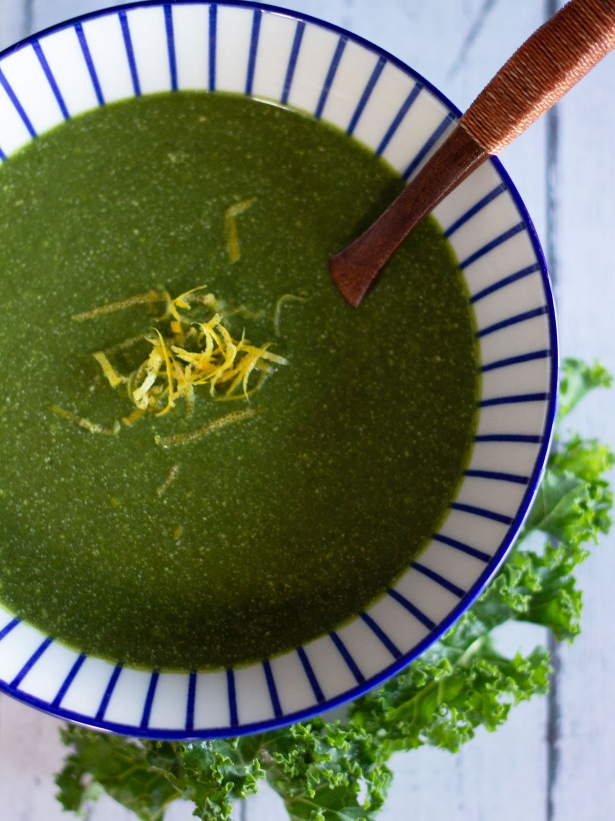 bowl of green soup topped with lemon zest