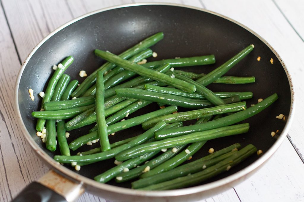 garlic and green beans in a frying pan