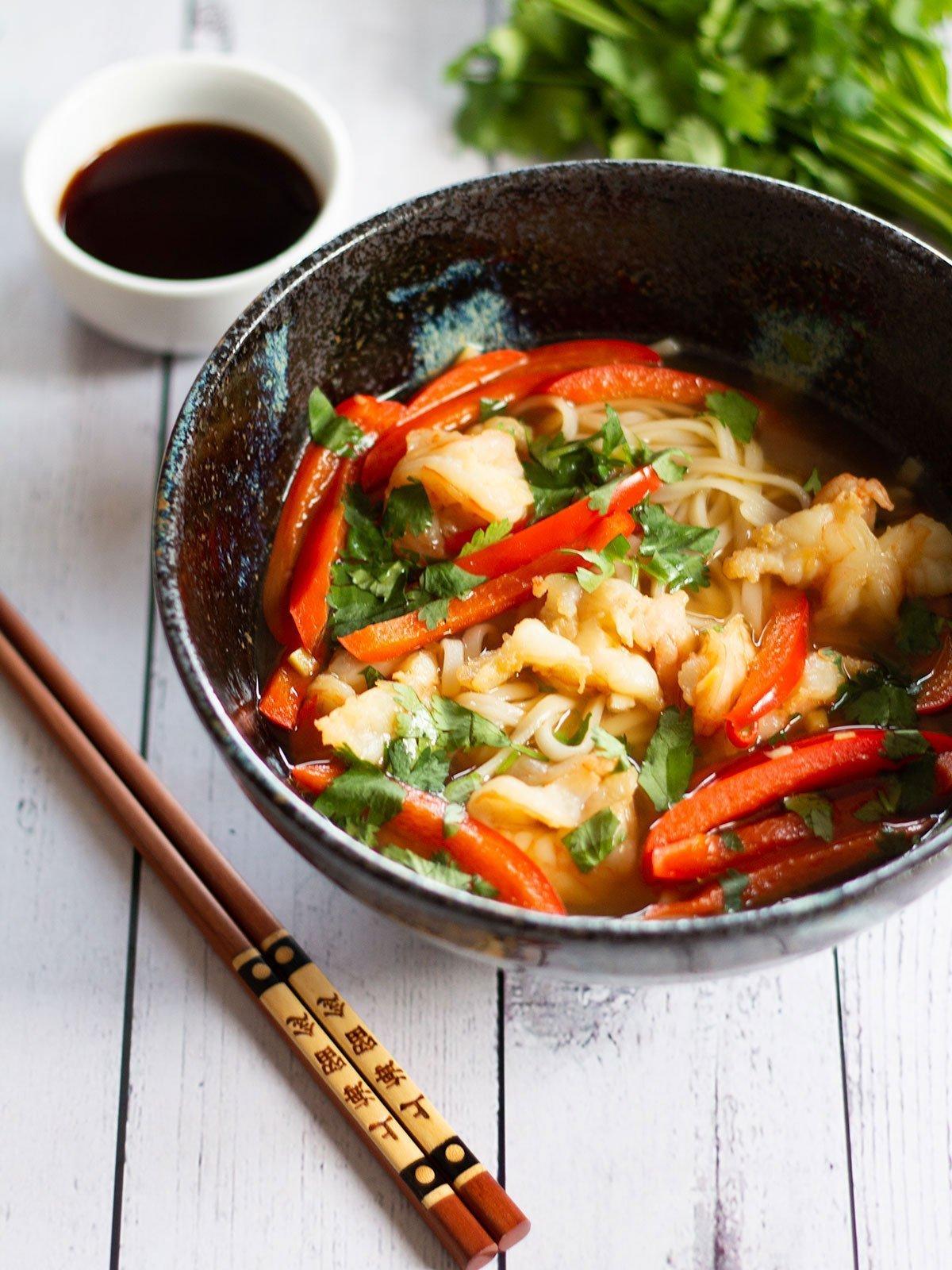 A bowl of prawn pho and chopsticks