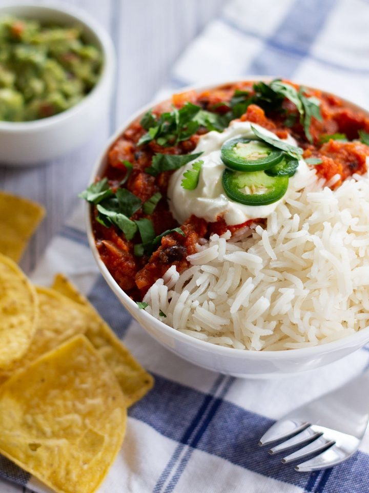 a bowl of sweet potato chilli with tortilla chips and guacamole