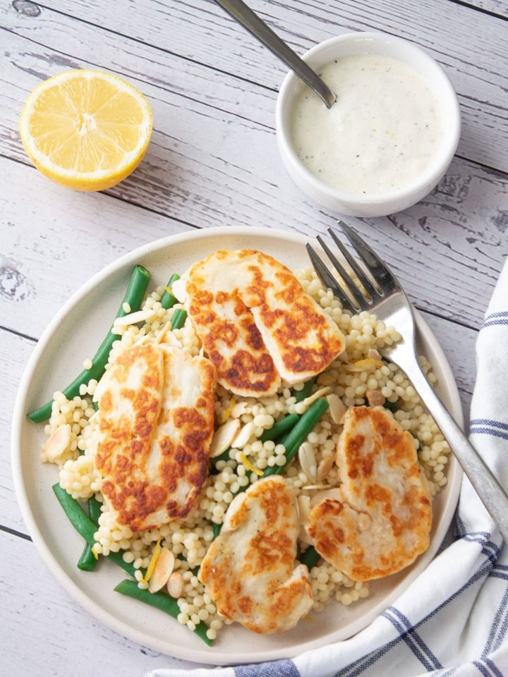 Giant Couscous & Halloumi Salad with dressing and lemon